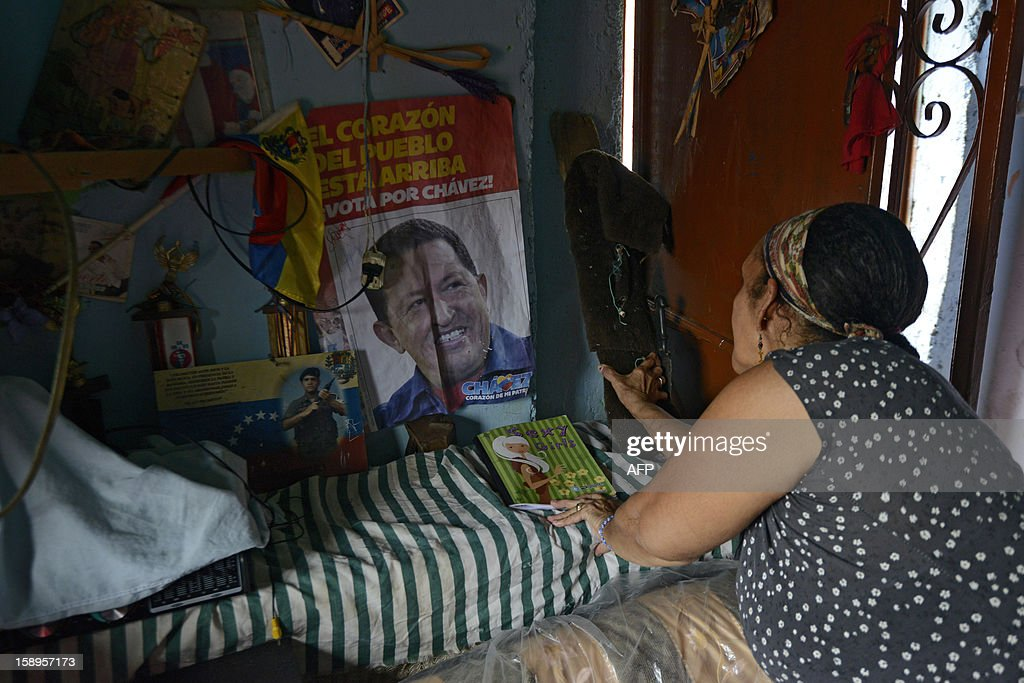 A woman fixes a poster of Venezuelan President Hugo Chavez at her home in the popular sector of San Agustin, in Caracas on January 4, 2013. Hugo Chavez's top aides have gone on the offensive, accusing the opposition and media of waging a 'psychological war,' as Venezuela's cancer-stricken president battles a serious lung infection. The closing of ranks followed a high-level gathering of top Venezuelan officials in Havana with Chavez, amid growing demands to know whether he will be fit on January 10 to take the oath of office for another six-year-term. AFP PHOTO/Leo Ramirez