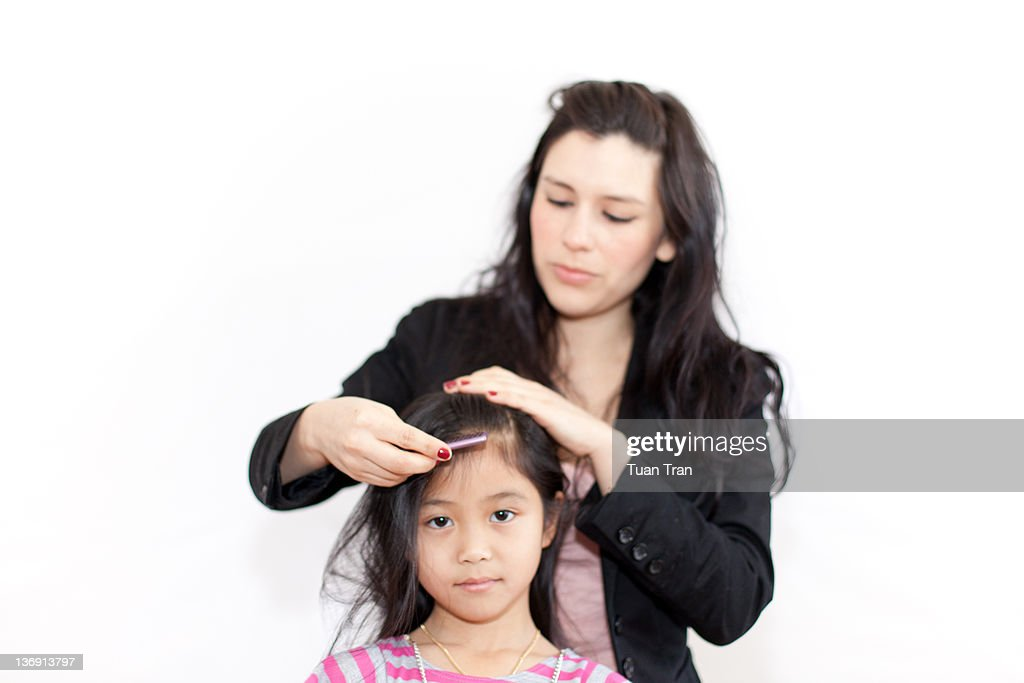 Woman fixing hair of girl : Stock Photo
