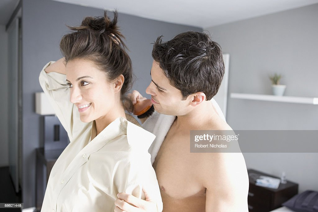 Woman fixing hair while husband watches : Stock Photo