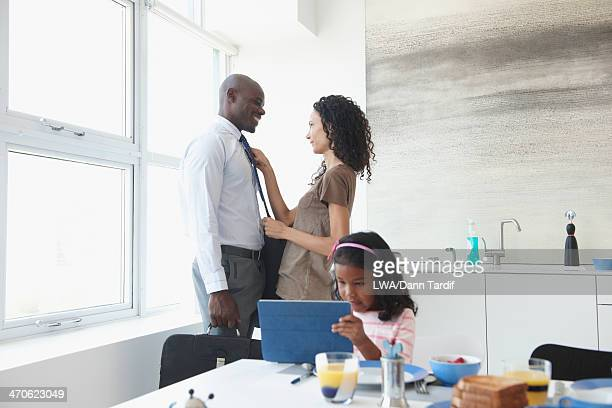 Woman fixing husband's tie in kitchen