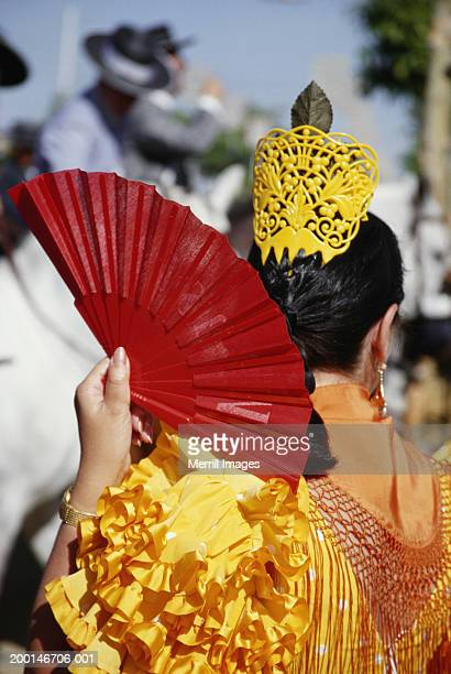 Woman flamenco dancing, holding fan, rear view