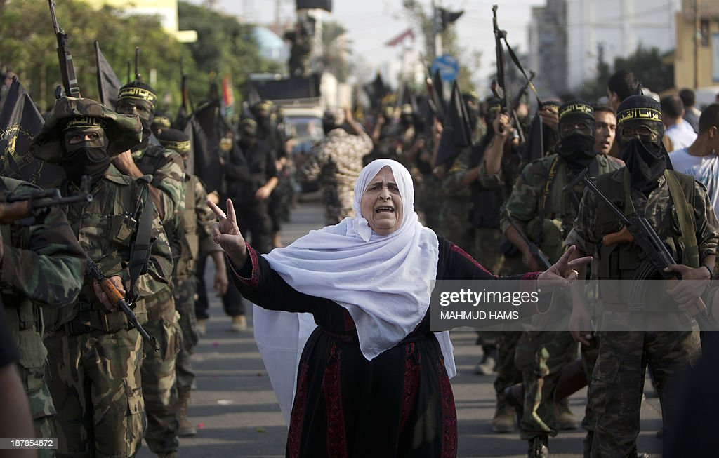 A woman flashes the sign of victory among members of the Palestinian Islamic Jihad movement parading with guns on November 13, 2013 in the streets of Gaza City during an anti-Israel march as part of the celebrations marking the first anniversary of Israel's Operation Pillar of Defence.