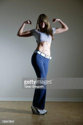 Woman flexing arm muscles, studio shot : Stock Photo