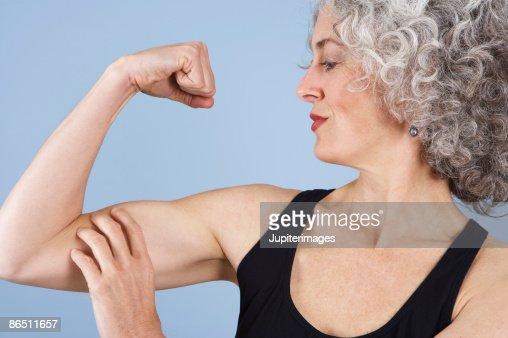 Woman flexing bicep : Stock Photo