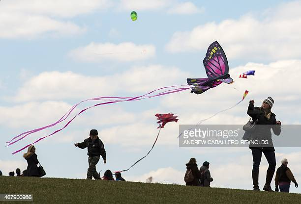 A woman flies a kite near the Washington Monument during the annual Blossom Kite Festival in Washington DC on March 28 2015 The event is part of the...