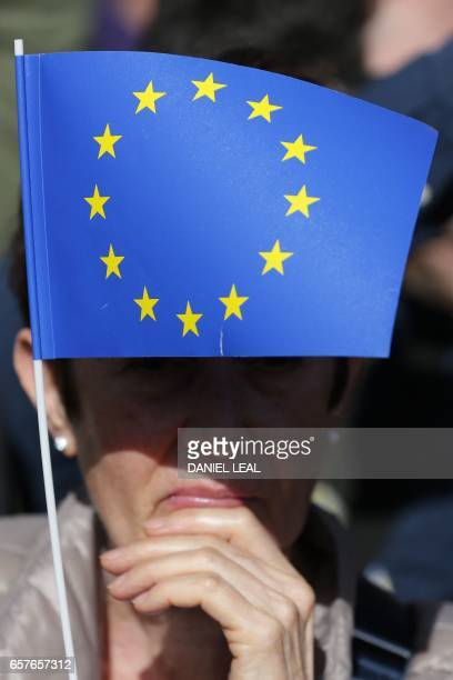 A woman flies a small EU flag in Parliament Square during an antiBrexit proEuropean Union march in central London on March 25 ahead of the British...