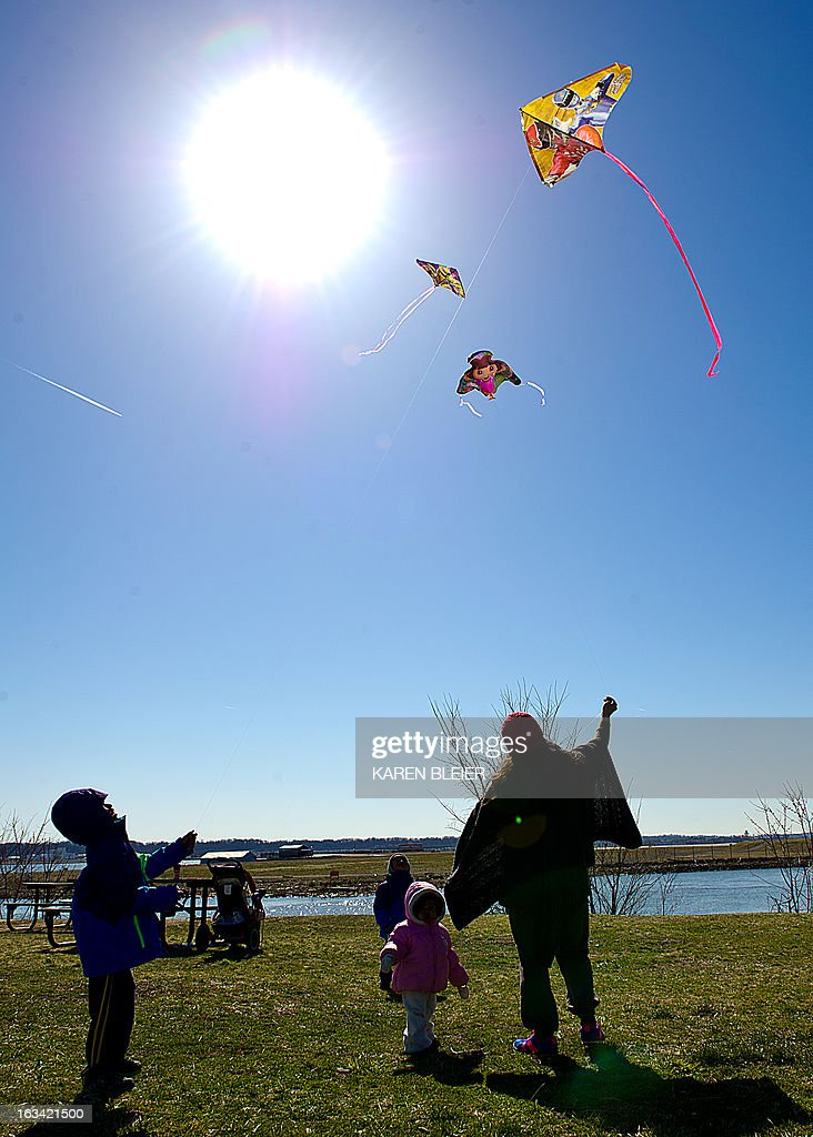 A woman flies kites with her children on a warm sunny day in Alexandria, Virginia, on March 9, 2013. The weather was in stark contrast to that of only a couple of days ago, when a winter storm hammered the East coast. AFP PHOTO / Karen BLEIER
