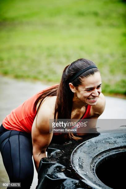 Woman flipping tractor tire outside during workout