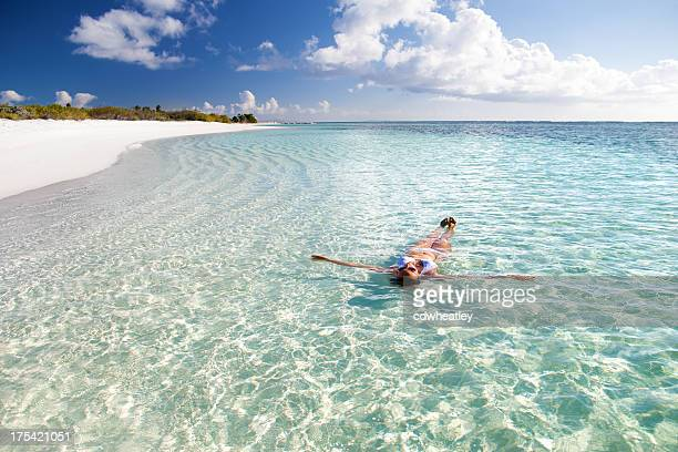 woman floating in crystal clear water at a Caribbean beach