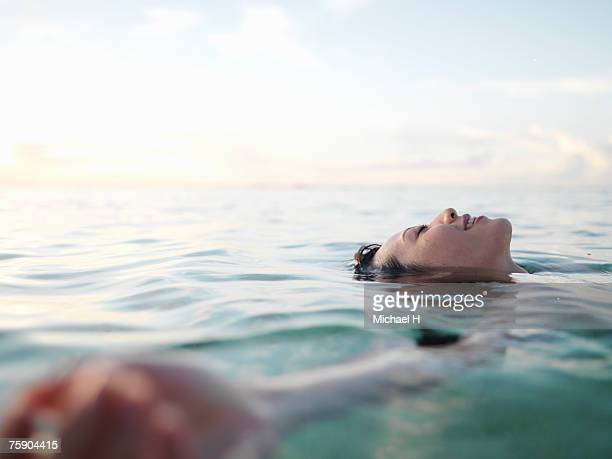 Woman floating in sea, smiling, profile