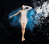 woman floating in water covered in blue material