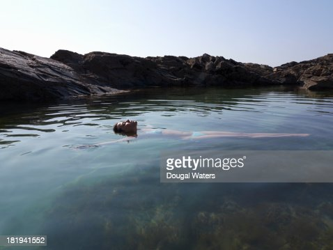 Woman floating on back in rock pool.