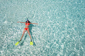 Woman floating on crystal clear waters with snorkeling gear