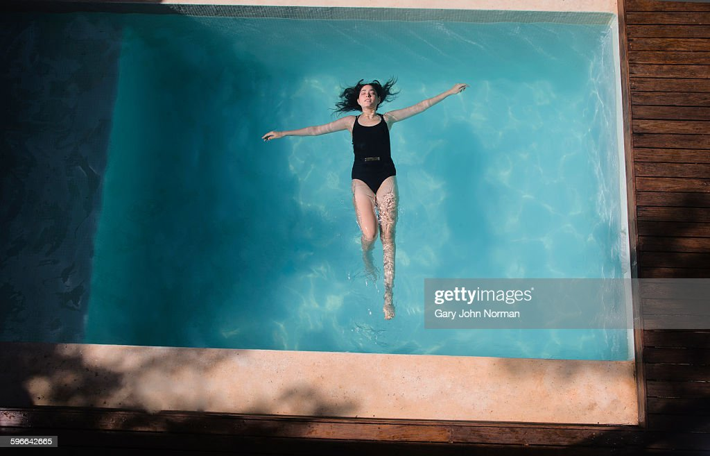 Woman floating on her back in pool.