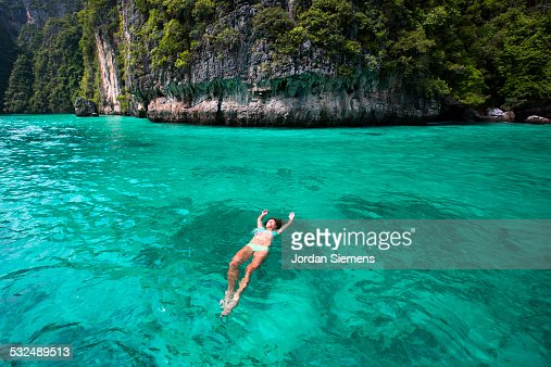 A woman floating on her back in tropical water.