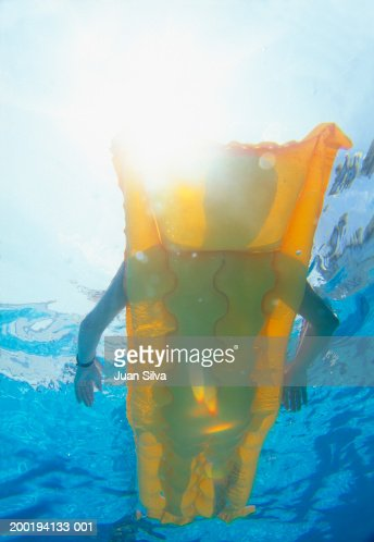 Woman floating on inflatable bed in pool (underwater view)