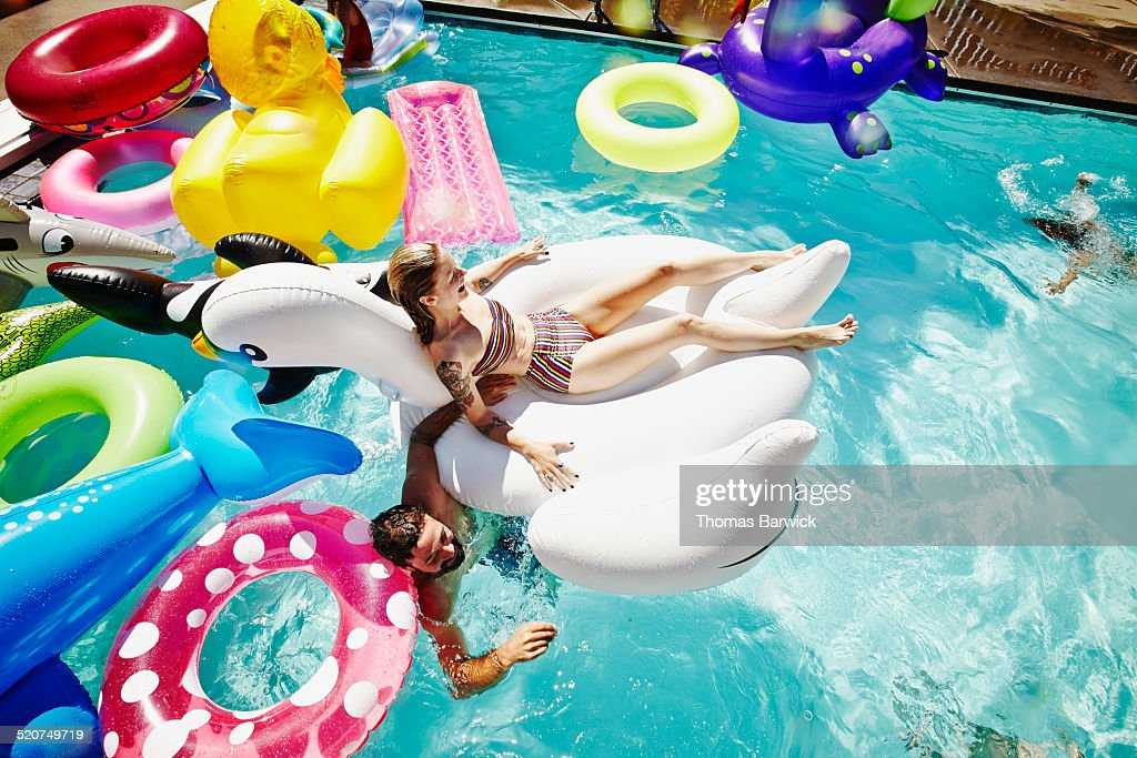 Woman floating on inflatable pool toy during party