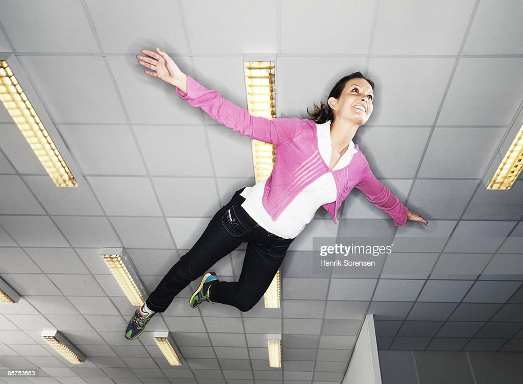 Woman floating under the ceiling. : Stock Photo
