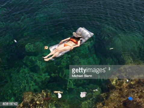 Woman floats in the sea amongst trash