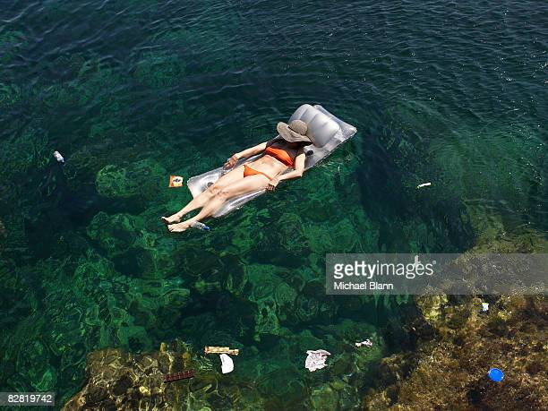 Woman floats in the sea amongst trash