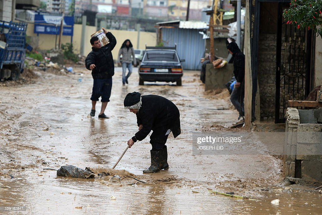 A woman flushes water and mud from the entrance of her flooded house in Beirut's southern impoverished suburb of Hayy al-Sellum on January 9, 2013 as heavy rains and high speed winds hit Lebanon. A met office official at Beirut airport said the storm would continue and that lower temperatures would result in snowfall in the mountains as low as 300 metres.