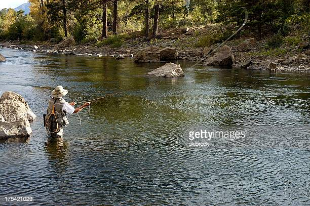 Woman fly fishing in flowing river