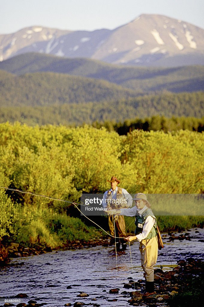 Woman flyfishing with man stock photo getty images for Fly fishing photography