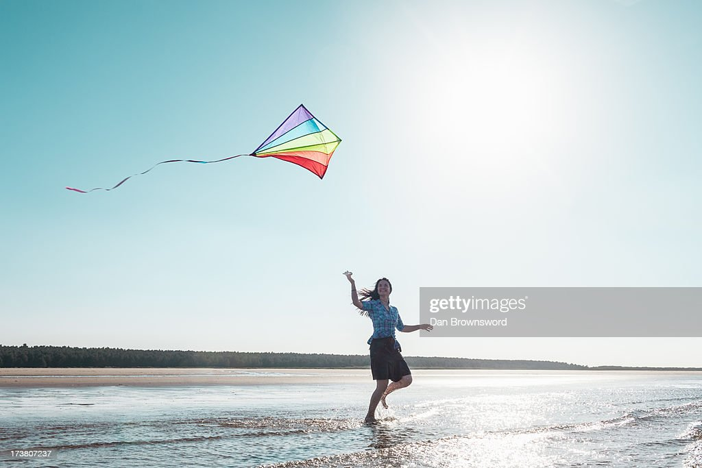 Woman flying kite on beach : Stock Photo