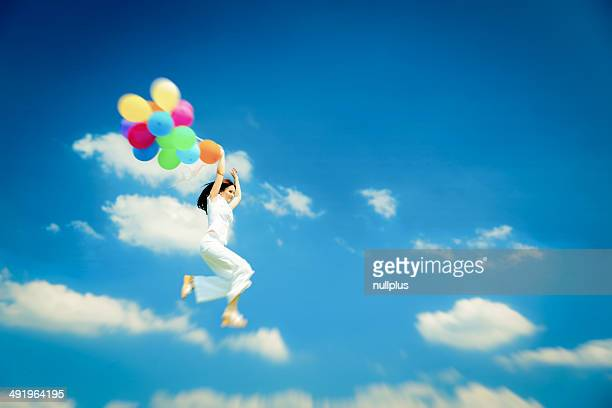 woman flying with colorful balloons
