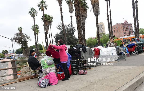 A woman folds clothes at a homeless encampment above a downtown Los Angeles freeway on May 12 2015 A report released by the Los Angeles Homeless...