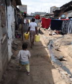 A woman followed by a toddler carries water jerricans as she goes to fetch water in the slum of Mathare one of the poorest slums in Nairobi on May 28...