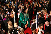 A woman follows Laurina Fleure carrying her long dress as she arrives at the 58th Annual Logie Awards at Crown Palladium on May 8 2016 in Melbourne...