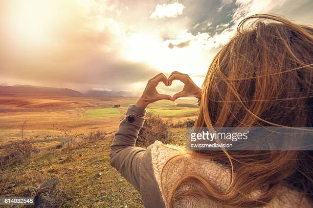 Woman frames nature into heart shape finger frame