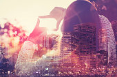 Woman framing the future. This is a montage which has a city scape overlaid. Success and vision concept