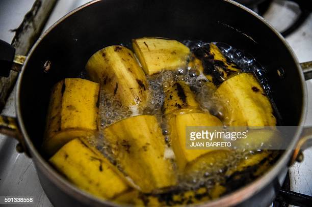 A woman fries plantains to make 'arepas' in Caracas on 16 August 2016 Pumpkin and beetroot arepas plantain peels pretending to be shredded meat...