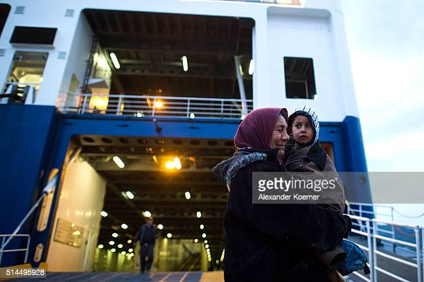 A woman from Afghanistan holds a child on her arm at the Port of Mytelene while boarding a ferry which will bring 500 refugees to Athens on March 9...