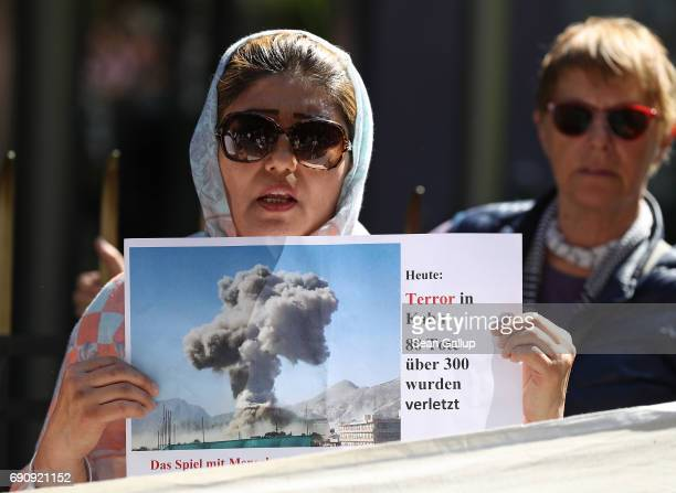 A woman from Afghanistan protesting against deportations holds up a photo of today's bombing in Kabul outside the Afghan Embassy on May 31 2017 in...