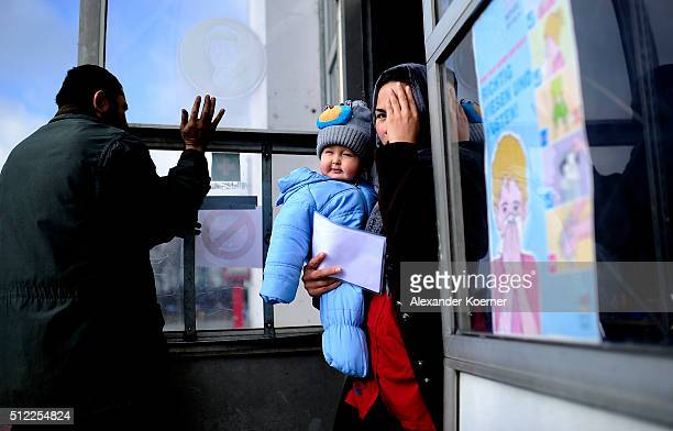 A woman from Afghanistan walks by a workshop while holding her son at the shelter where they live while their asylum applications are processed on...