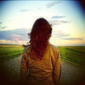 Woman from behind looks down gravel road