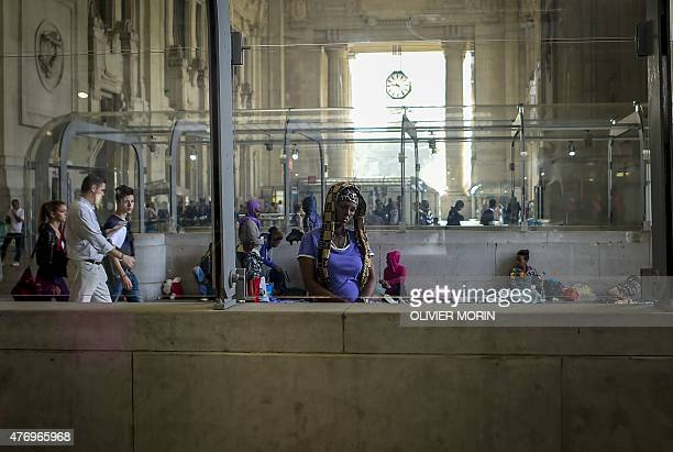 A woman from Eritrea part of a group of migrants looks on at the Milan train station on June 13 as hundreds migrants arrived in Milan late on June 10...