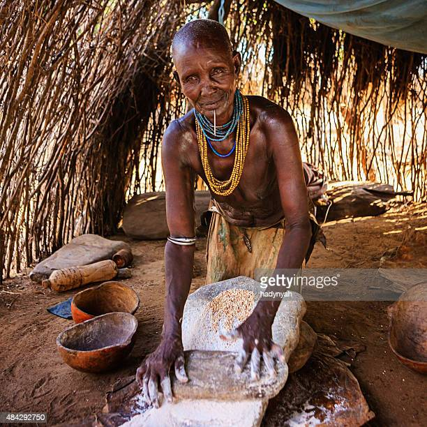 Woman from Karo tribe making sorghum flour, Ethiopia, Africa