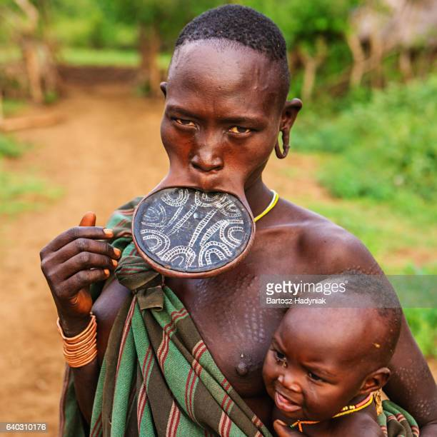 Woman from Mursi tribe breasfeeding her baby, Ethiopia, Africa