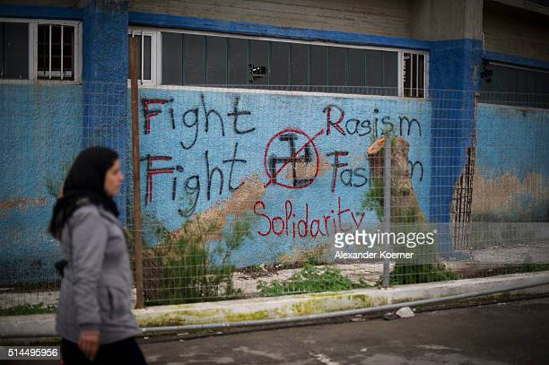 A woman from Syria walks by a graffity `Fight Racism Fight Fachism Soildarity« at the Port of Mytelene prior boarding a ferry which will bring 500...