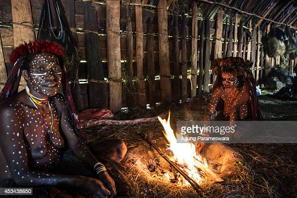 A woman from the Dani burns sweet potatoes at Obia Village on August 9 2014 in Wamena Papua IndonesiaThe Dani tribe live a traditional existence in...