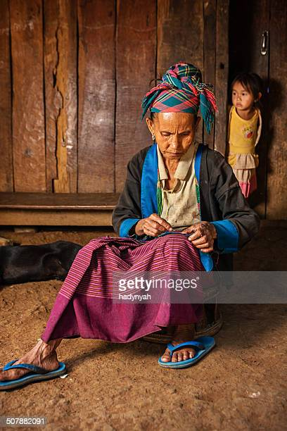 Woman from the hill tribe sewing a pillow