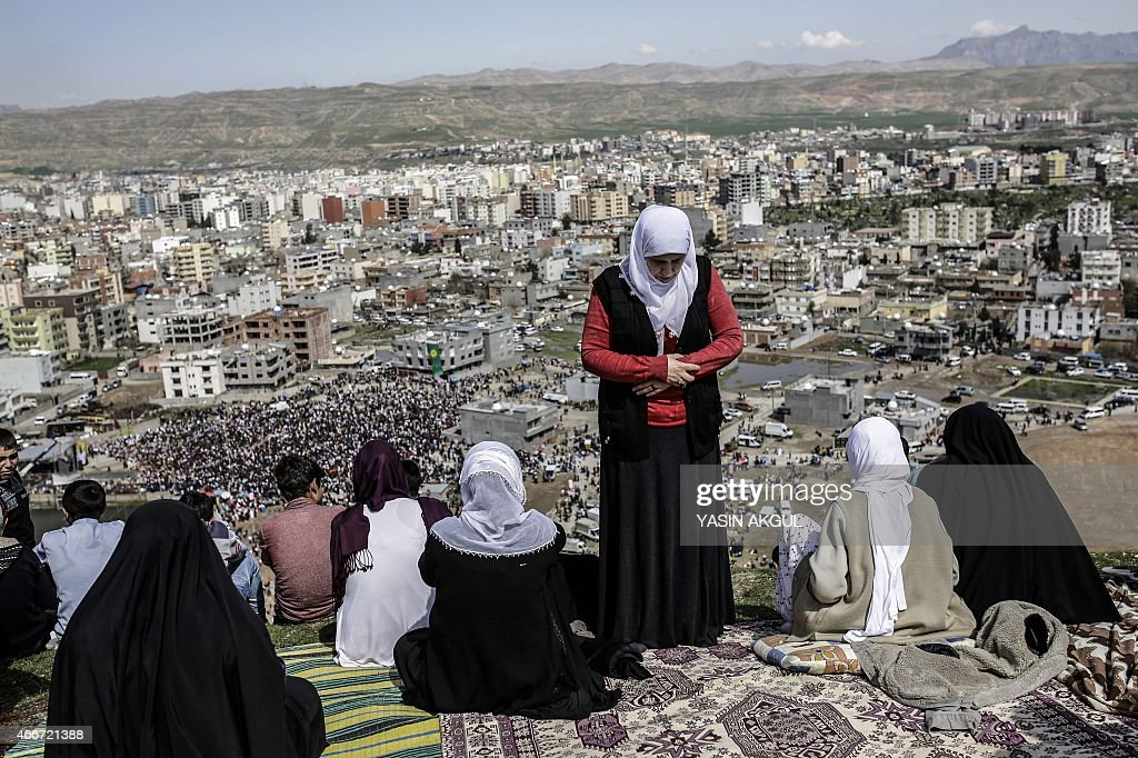 A woman from the Kurdish community offers prayers as people gather to celebrate Newroz which marks the arrival of spring and the new year in Cizre in...