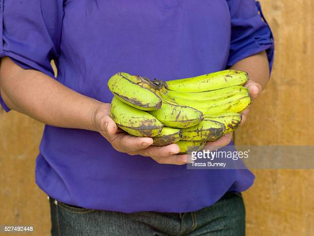 A woman from the local Women's farmer group in Sitio Matinao holding a bunch of bananas she is selling at Alamada market Cotabato Province Mindanao...