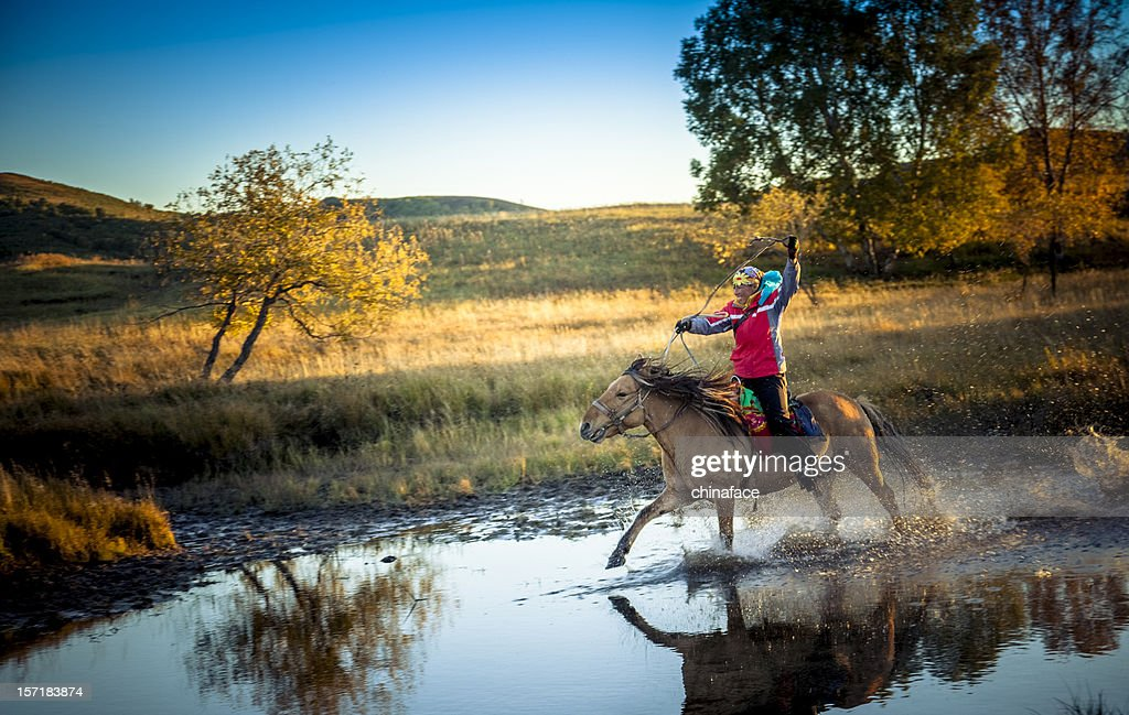 woman gallops horse through stream