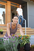 Woman gardening, man on porch in background (focus on woman)