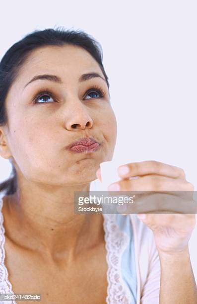 woman gargling and holding a cup of mouthwash